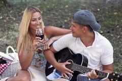 对他的弹吉他的夫人的微笑的人唱歌小夜曲 免版税库存照片