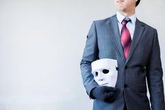 对他的表明事务的身体的商人运载的白色面具 免版税库存图片