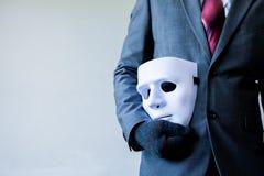 对他的表明企业欺骗和伪造企业合作的身体的商人运载的白色面具 免版税图库摄影
