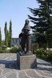 对18第19个世纪的一个人的纪念碑在正方形的在大厦前面,围拢由开花的花床 免版税图库摄影