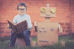 读对从纸板箱的机器人的一个小男孩户外 免版税库存照片