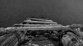对水线的老木梯子 免版税库存图片