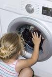 对洗衣机感兴趣的孩子 库存照片