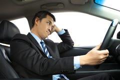 对负顶头和驾驶汽车的沮丧的商人 免版税库存图片