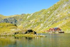 对Balea湖村庄的白天视图与绿色山 免版税库存图片