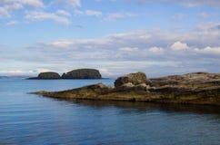 对Ballintoy港口的入口北爱尔兰北部安特里姆海岸的有它的石被修造的船库的在一天在春天 免版税库存图片
