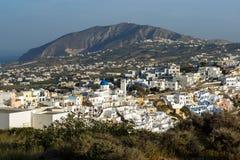 对Fira和先知伊莱亚斯峰顶,圣托里尼海岛,锡拉,希腊镇的惊人的风景  免版税库存照片
