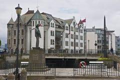 对Fisher男孩雕象的看法与在背景的老大厦在Alesund,挪威 库存照片