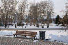 对Iset的长凳和叶卡捷琳堡citiscape在冬天耸立 库存照片