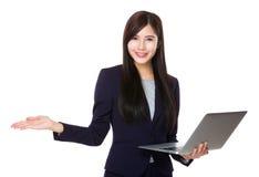 对laptopa和开放手棕榈的亚洲女实业家用途 免版税库存照片