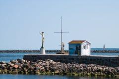 对Warnemunde港口的入口包括Esperanda金黄雕象 免版税库存图片