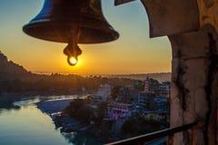 从寺庙的看法在河甘加和拉克什曼Jhula桥梁的巨大的响铃下在日落 瑞诗凯诗 免版税图库摄影