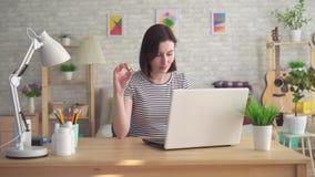 寻找关于互联网的信息膝上型计算机的和拿着一个助听器的年轻女人 股票录像