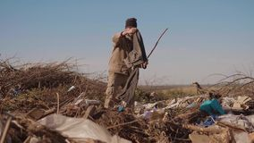 寻找在包裹的生活方式转储饮料的肮脏的男性无家可归的饥饿的人衣物食物与走去 股票视频