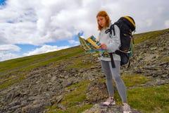 寻找在地图的红头发人女孩游人一条路线在她的h 免版税库存图片