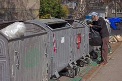 寻找在大型垃圾桶的老人塑料瓶,大型垃圾桶潜水 库存照片