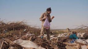 寻找在生活方式的转储的肮脏的男性无家可归的饥饿的人衣物食物与走的包裹去看 股票视频
