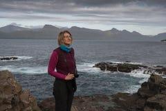 寻找在fa的峭壁的妇女摄影师一个主题 库存照片