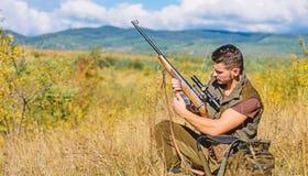 寻找射击战利品 与寻找动物的步枪的猎人 寻找爱好和休闲 充电的人寻找步枪 免版税图库摄影