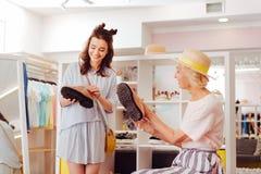 寻找新的鞋子的购物的上瘾的母亲和女儿 免版税库存图片