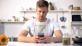 寻找烹饪食谱的围裙的帅哥在互联网,厨房新手 库存照片