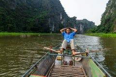导游在的Trang用浆划沿Ngo东河的一条小船 免版税库存照片