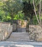 导致一个公园、石墙和篱芭铁门的上升的大理石台阶 免版税库存照片