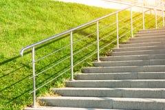 导致与草坪草的石楼梯倾斜,当金属发光和用栏杆围 免版税库存图片