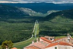 导致从有很远红色铺磁砖的屋顶的镇的漫长的路的美丽的景色与青山的天际 免版税库存图片