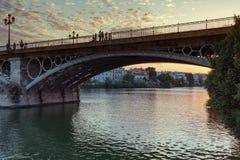 导致从老镇的桥梁瓜达尔基维尔河河的历史的特里亚纳区在塞维利亚,西班牙 免版税库存照片