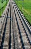 导致天际的几个铁轨在绿色领域中间  免版税库存图片
