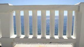 导致完善的蓝色海和海滩的白色台阶 与经典白色楼梯栏杆和空的大阳台的夏天视图 股票录像