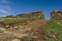导致对在石块墙的一个孔的土道路有清楚的蓝天的在背景中 免版税库存照片