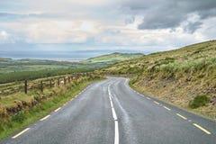 导致有海滩口岸和山的一个镇的路的遥远的看法 美好的风景和领域 爱尔兰凯利环形 免版税库存图片