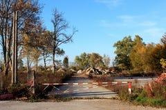 导致被放弃的建造场所的闭合的长满的被铺的路 库存图片