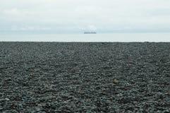 导致银蓝色海的一个有卵石花纹的海滩 图库摄影