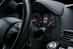 导航在一辆现代汽车的方向盘按有黑穿孔的皮革内部的 现代汽车内部细节 免版税图库摄影