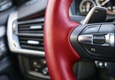 导航在一辆现代汽车,汽车内部细节的红色方向盘按 免版税图库摄影