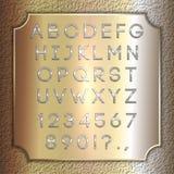 导航银色上漆的字母表信件、数字和标点在黄铜背景板材 图库摄影