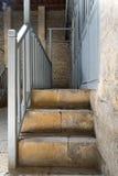 导致一个狭窄的段落的石楼梯构筑由蓝色木门和楼梯栏杆 免版税库存照片