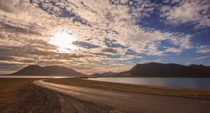 导致与五颜六色的cloudscape的山的美丽的空的路桥梁在冰岛 免版税库存图片