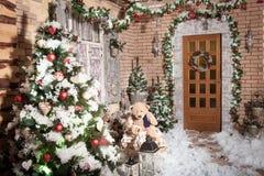 导致冬天房子的门的树桩道路有圣诞节花圈的 库存照片