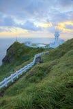导致在峭壁的一座灯塔的供徒步旅行的小道在台湾北海岸在日出 免版税库存图片