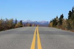 导致在秋天的积雪的山的高速公路路 免版税库存图片