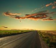 导致天际的偏僻的路在日落天空 库存图片