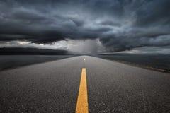 导致山的空的高速公路通过雨 免版税图库摄影