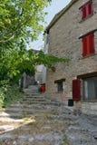 导致有红色窗口的一个村庄房子的一条石道路 库存照片