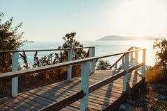 导致海滨的木走道反对日落晴朗的夏天海滩松弛概念Gelendzhik背景  库存图片
