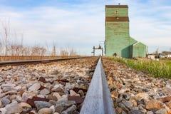 导致老绿色谷物仓库的路轨 免版税库存照片