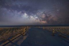 导致银河星系的海滩道路 免版税库存照片